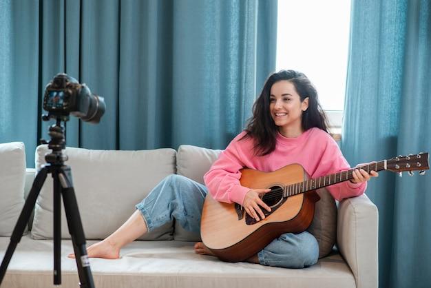 Blogger sentado e tocando violão no sofá
