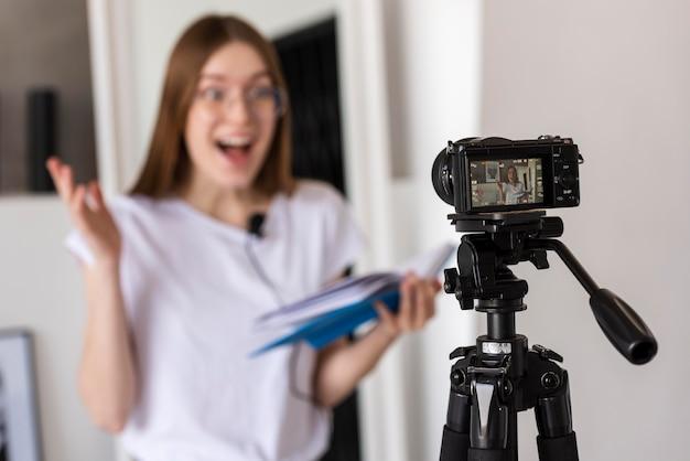 Blogger surpreso gravando com câmera profissional, segurando um livro
