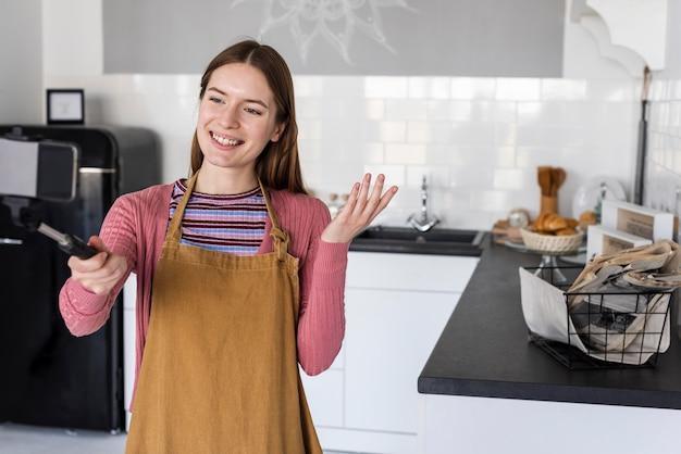 Blogger usando selfie stick e mostrando sua cozinha