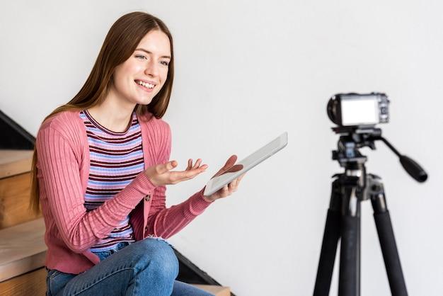Blogger usando tablet e conversando com a câmera