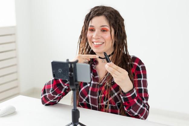 Blogging, vlog e conceito cosmético - jovem blogueira falando para a câmera sobre batom preto.