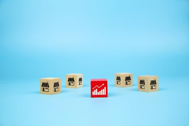 Blogs de brinquedo de madeira cubo com ícone de loja e ícone de gráfico de marketing de franquia para o crescimento dos negócios.