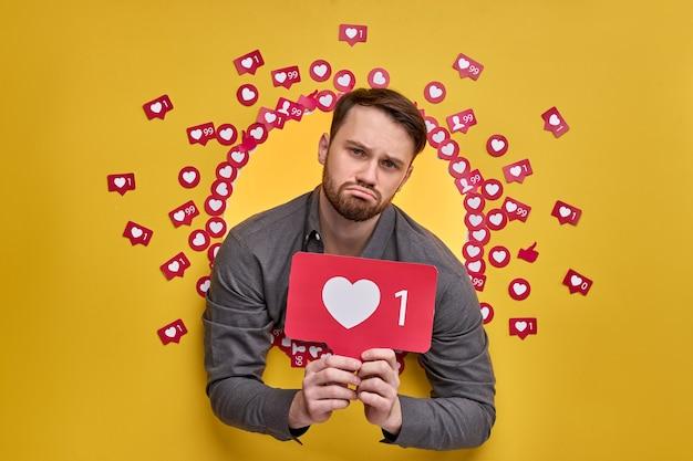 Blogs na internet. retrato de um homem chateado segurando um ícone em forma de coração, recomendando clicar