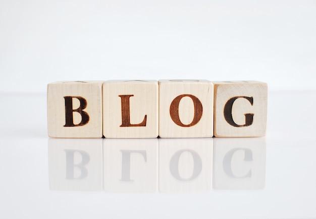Blogue da palavra feito com cubos de madeira, fundo branco com reflexão.