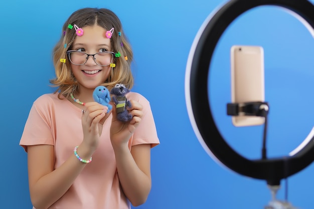 Blogueira adolescente fala sobre artesanato feito à mão em uma transmissão online em seu smartphone para assinantes de redes sociais e contas