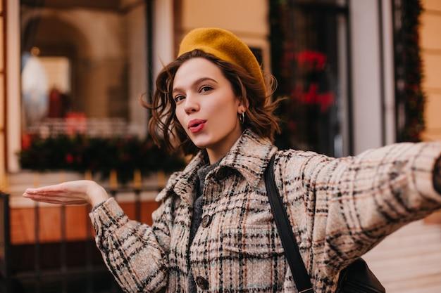 Blogueira ativa e estilosa fazendo selfie na parede de um belo prédio