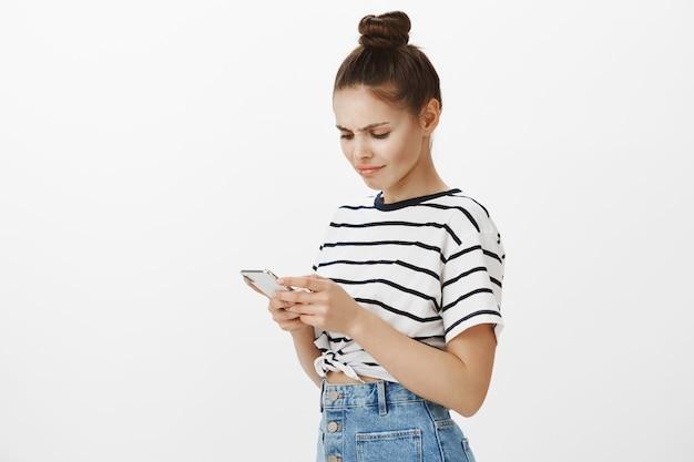 Blogueira atraente confusa e relutante franzindo a testa enquanto lê algo na tela do smartphone