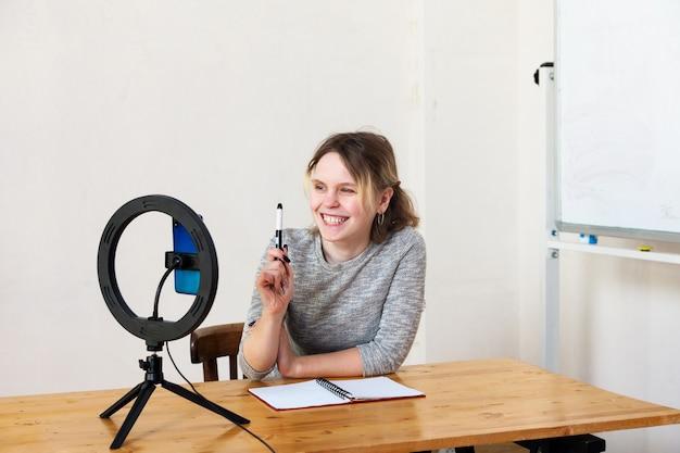Blogueira de 15 anos conduz uma transmissão ao vivo e se ilumina com uma luminária em uma sala iluminada