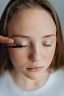 Blogueira de beleza aplicando rímel em sua modelo