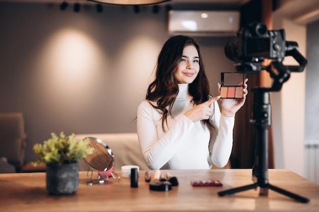 Blogueira de beleza bela mulher filmando tutorial de rotina de maquiagem diária na câmera. avaliação de produtos cosméticos de transmissão ao vivo de jovem influente em um estúdio caseiro. trabalho de vlogger. mostrando produtos de maquiagem.