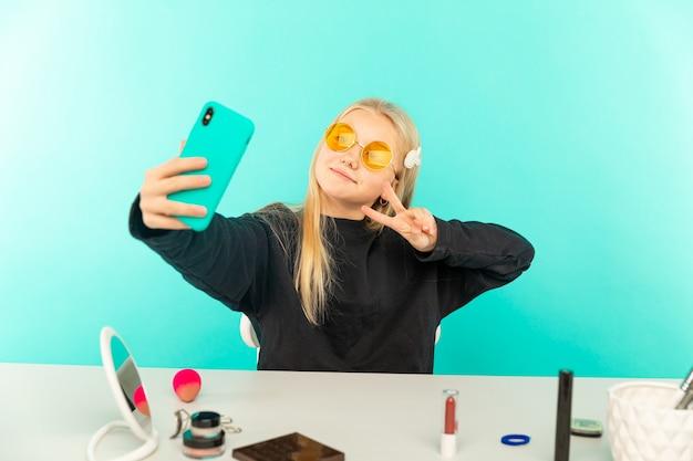 Blogueira de beleza feminina. adolescente loira posando para a câmera e fazendo um vlog.