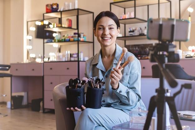 Blogueira de beleza feminina feliz gravando vlog de consultoria escolhendo escova para aplicação de cosméticos