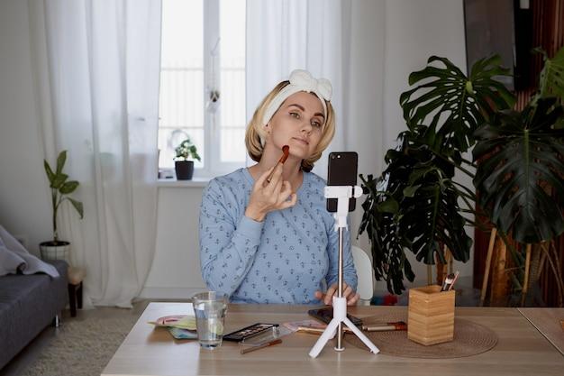 Blogueira de beleza feminina grava podcast para assinantes sobre conceito de maquiagem, transmissão e blogging