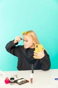 Blogueira de beleza garota fazendo vlog isolado sobre o estúdio azul.