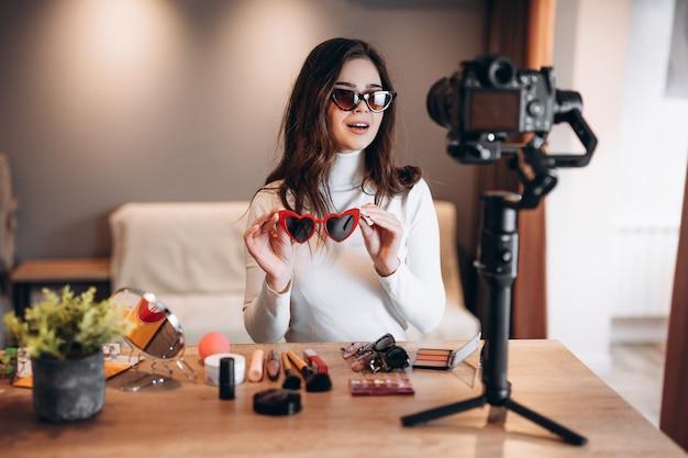 Blogueira de beleza muito feminina em óculos de sol, filmando o tutorial de rotina de maquiagem diária na câmera.