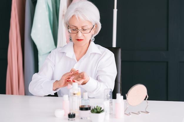 Blogueira de beleza sênior. mulher idosa fazendo revisão de vídeo