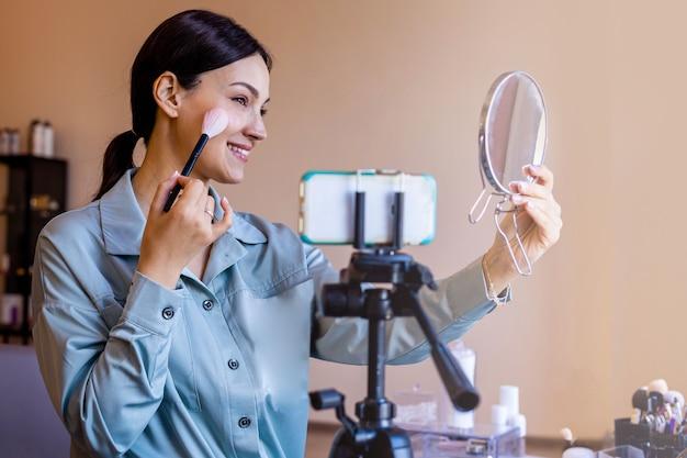 Blogueira de beleza visagista feminina aplicando pincel, uso de maquiagem e filmagem de espelho usando smartphone