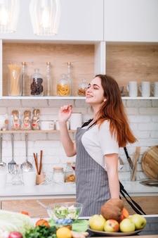 Blogueira de comida dançante. fã de nutrição saudável. ótimo humor. mulher jovem sorridente usando avental dançando na cozinha.