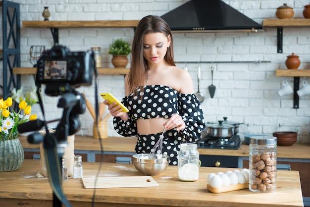 Blogueira de comida de menina muito jovem com vestido de bolinhas, trabalhando em um novo vídeo e explicando como cozinhar um prato.