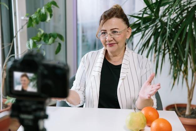 Blogueira de culinária sênior, gravando vídeo sobre alimentação saudável. mulher idosa vlogger de estilo de vida prepara um novo vídeo para seu canal e se comunica com os seguidores.