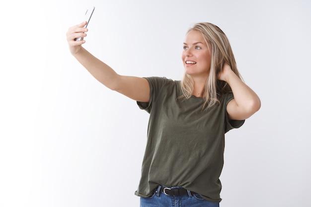 Blogueira de estilo de vida feminino elegante tomando selfie no smartphone, verificando o corte de cabelo, estender a mão com o celular, fazer uma boa foto falando com videochamada sobre fundo branco, sorrindo para a tela do gadget