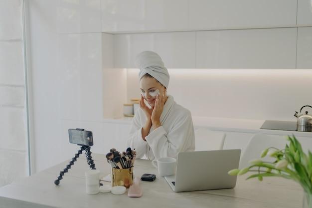 Blogueira de jovem atraente aplicando adesivos cosméticos sob os olhos, gravando vídeo em smartphone para vlog de beleza, criando conteúdo para mídia social enquanto está sentado na cozinha moderna. conceito de cuidados com a pele