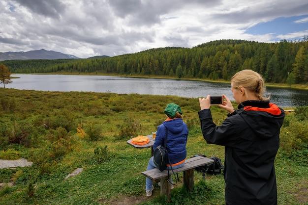Blogueira de jovem tira uma foto de sua amiga por trás contra um lago de montanha. piquenique turístico no fundo de belas montanhas cobertas por floresta de coníferas.