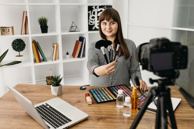 Blogueira de maquiagem feminina com streaming com câmera e laptop