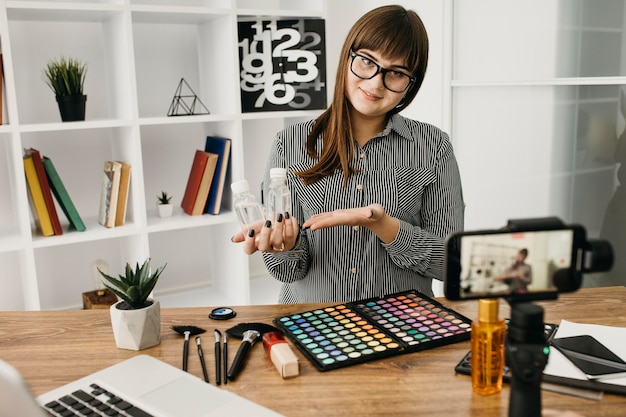 Blogueira de maquiagem feminina com streaming com smartphone e laptop em casa