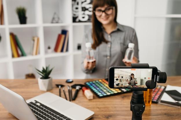 Blogueira de maquiagem feminina com streaming com smartphone e laptop
