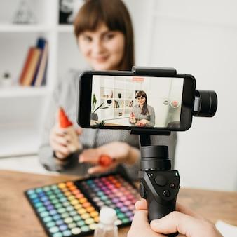 Blogueira de maquiagem feminina com streaming com smartphone