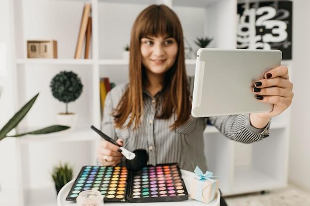 Blogueira de maquiagem feminina com streaming com tablet em casa
