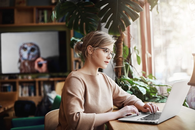 Blogueira de moda bem-sucedida e bonita escrevendo um novo ensaio em um laptop enquanto está sentado em um café e esperando por um café, olhando para a tela enquanto navega na internet, usando a web para criar novos conteúdos.