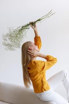 Blogueira de moda com flores secas em uma imagem estilosa em um fundo cinza. poster