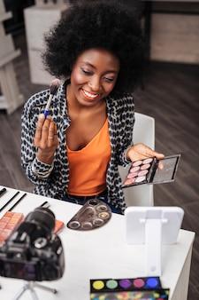 Blogueira de moda. mulher bonita de pele escura com batom coral segurando paleta de blush enquanto fala para a câmera