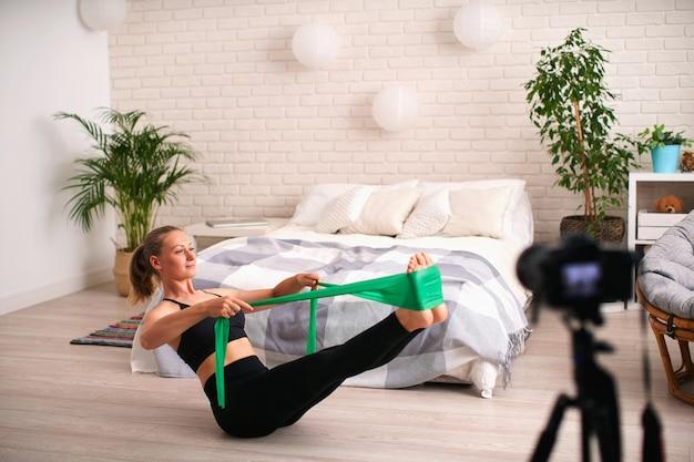 Blogueira de mulher em sportswear grava vídeo na câmera enquanto ela faz exercícios em casa