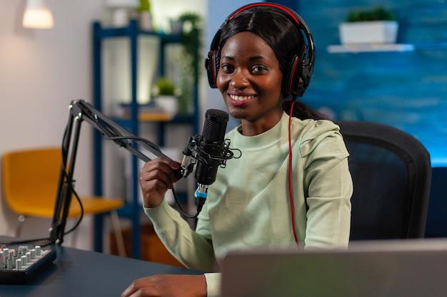 Blogueira de mulher sentada em um estúdio em casa, olhando para a câmera para um show de podcast de gravação ao vivo. falando durante a transmissão ao vivo, blogueiro discutindo no podcast usando fones de ouvido.