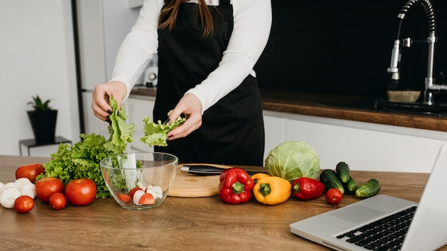 Blogueira fazendo streaming de culinária em casa com laptop