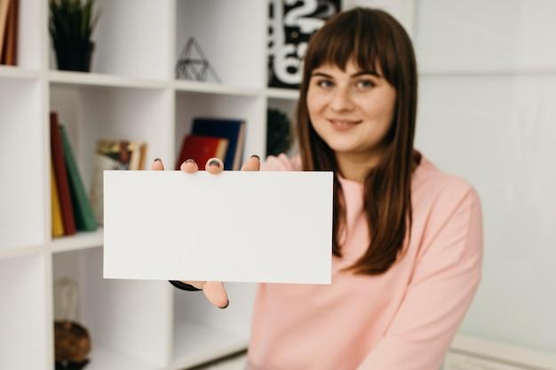 Blogueira fazendo streaming em casa segurando papel