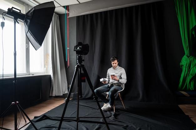Blogueira feliz fazendo revisão de vídeo do novo celular, abrindo a caixa com um dispositivo moderno, filmando conteúdo para seu vlog dentro de casa.