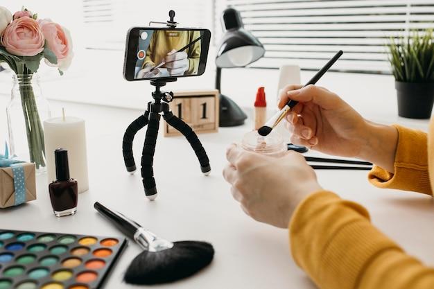 Blogueira feminina fazendo streaming de maquiagem online com smartphone