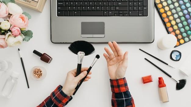 Blogueira feminina fazendo streaming de produtos de maquiagem online com laptop