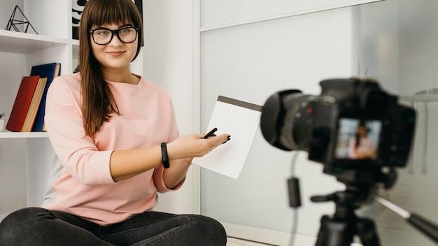 Blogueira feminina fazendo streaming em casa com câmera e notebook