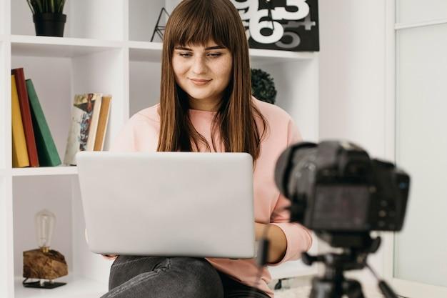 Blogueira feminina fazendo streaming em casa com laptop e câmera