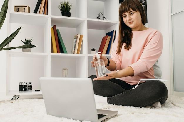Blogueira feminina fazendo streaming em casa com laptop e desinfetante para as mãos