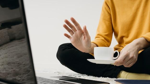 Blogueira feminina fazendo streaming em casa com laptop e xícara de café