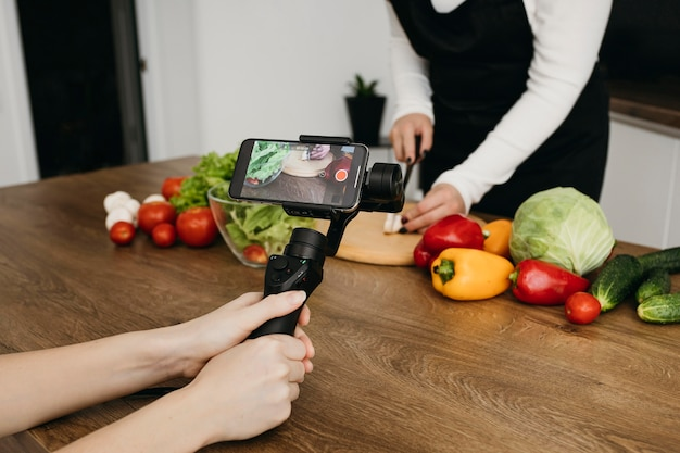 Blogueira feminina gravando a si mesma enquanto prepara comida