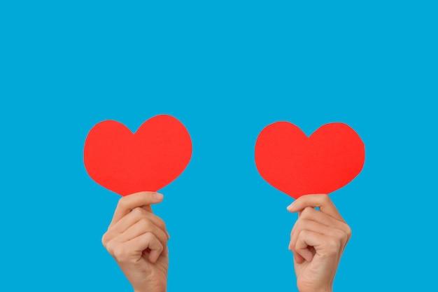 Blogueira feminina segura nas mãos pequenos corações vermelhos, dançando ao ritmo da música isolado sobre fundo azul. como o conceito de ternura de rede social de blogging. dia dos namorados mulheres internacionais