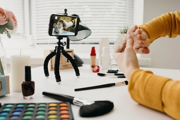 Blogueira feminina streaming de produtos de maquiagem online com smartphone