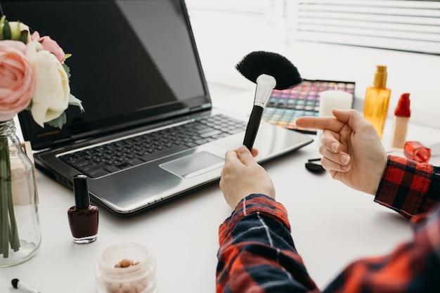 Blogueira feminina transmitindo pincéis de maquiagem online com laptop